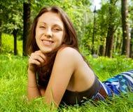 Mujer sonriente joven en la hierba Fotografía de archivo libre de regalías