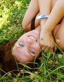 Mujer sonriente joven en la hierba Foto de archivo libre de regalías