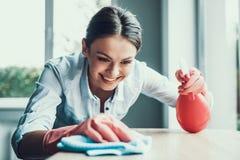 Mujer sonriente joven en los guantes que limpian la casa fotos de archivo libres de regalías
