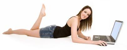 Mujer sonriente joven en suelo usando la computadora portátil Foto de archivo