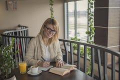 Mujer sonriente joven en un restaurante que lee un libro y tomar ningún imagen de archivo