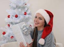 Mujer sonriente joven feliz de conseguir su presente para la Navidad Foto de archivo