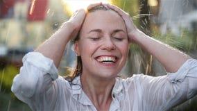 Mujer sonriente joven feliz que se divierte en tiempo lluvioso Señora alegre Has Wet Hair en parque del verano metrajes