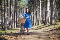 Mujer sonriente joven hermosa con el pelo oscuro corto y el sombrero que colocan la bicicleta cercana con la cesta de ramo enorme Imagen de archivo libre de regalías