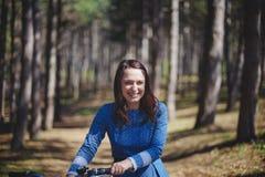Mujer sonriente joven hermosa con el pelo oscuro corto y el sombrero que colocan la bicicleta cercana con la cesta de ramo enorme Imágenes de archivo libres de regalías