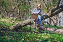 Mujer sonriente joven hermosa con el pelo oscuro corto y el sombrero que colocan la bicicleta cercana con la cesta de ramo enorme Foto de archivo libre de regalías