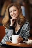 Mujer sonriente joven hermosa con una taza de café en un café Fotos de archivo