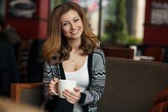 Mujer sonriente joven hermosa con una taza de café en un café Fotografía de archivo libre de regalías