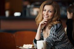 Mujer sonriente joven hermosa con una taza de café en un café Fotografía de archivo