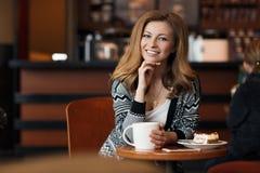 Mujer sonriente joven hermosa con una taza de café en un café Foto de archivo libre de regalías