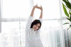 Mujer sonriente joven hermosa de la mujer asiática que se sienta en cama y str fotos de archivo