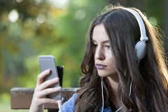 Mujer sonriente joven hermosa que escucha la música, sosteniendo un mobi Fotografía de archivo libre de regalías