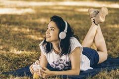 Mujer sonriente joven hermosa que escucha la música y que lleva a cabo la mañana Imágenes de archivo libres de regalías