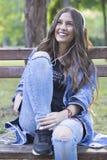 Mujer sonriente joven hermosa que se sienta en un banco en el parque y Fotografía de archivo libre de regalías