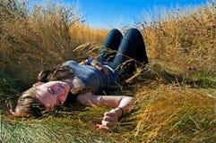 Mujer sonriente joven que coloca en campo de hierba amarillo largo con el fondo del cielo azul Imágenes de archivo libres de regalías
