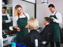 Mujer sonriente joven que corta el pelo femenino del pensionista Imagen de archivo