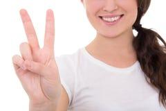 Mujer sonriente joven que da el signo de la paz aislado en blanco Imagen de archivo