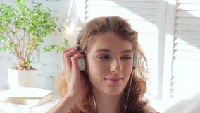 Mujer sonriente joven que escucha la música con los auriculares en una mañana soleada almacen de video
