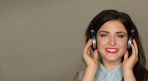 Mujer sonriente joven que escucha la música de los auriculares Fotografía de archivo