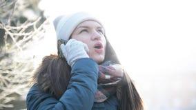 Mujer sonriente joven que habla con alguien por Smartphone en Sunny Morning Outdoors Muchacha hermosa en el sombrero blanco y almacen de metraje de vídeo