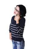 Mujer sonriente joven que habla en el teléfono Fotografía de archivo