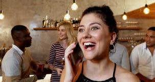 Mujer sonriente joven que habla en el teléfono mientras que amigos que obran recíprocamente en el fondo 4K 4k almacen de video