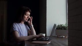 Mujer sonriente joven que habla en el teléfono y que mecanografía en un ordenador portátil almacen de metraje de vídeo