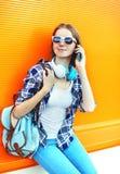 Mujer sonriente joven que habla en smartphone sobre colorido Foto de archivo libre de regalías