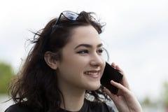 Mujer sonriente joven que habla en un teléfono móvil Imágenes de archivo libres de regalías