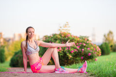 Mujer sonriente joven que hace ejercicios deportivos al aire libre Entrenamiento femenino del modelo de la aptitud afuera en el p Imágenes de archivo libres de regalías