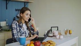 Mujer sonriente joven que hojea medios sociales usando el ordenador portátil y que habla el teléfono durante el desayuno por la m Foto de archivo