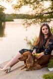 Mujer sonriente joven que juega con su perro en el jardín, ella está abrazando su animal doméstico imagen de archivo