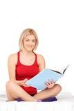 Mujer sonriente joven que lee un libro en una cama Fotografía de archivo