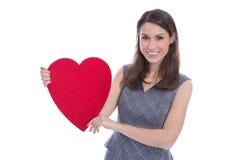 Mujer sonriente joven que lleva a cabo un corazón rojo grande. Imagen de archivo