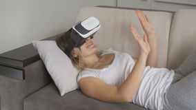 Mujer sonriente joven que miente en cama y vídeo de observación de 360 grados en auriculares de VR Cantidad tirada en la resoluci almacen de metraje de vídeo