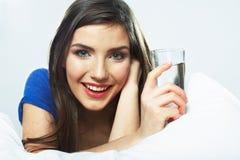 Mujer sonriente joven que miente en la cama, vidrio de agua del control Fotografía de archivo