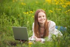 Mujer sonriente joven que miente en la hierba con el cuaderno en el parque que mira a la cámara Foto de archivo