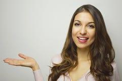 Mujer sonriente joven que muestra con la palma abierta de la mano su producto en el fondo blanco Copie el espacio Imagenes de archivo