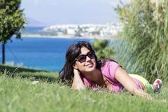 Mujer sonriente joven que pone en un prado verde con una opinión del mar Pulgares para arriba Imagen de archivo libre de regalías