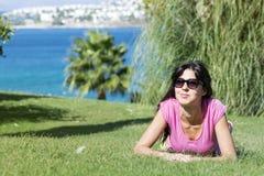 Mujer sonriente joven que pone en un prado verde con una opinión del mar Pulgares para arriba Imagenes de archivo