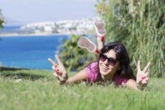 Mujer sonriente joven que pone en un prado verde con una opinión del mar Pulgares para arriba Fotografía de archivo