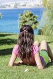 Mujer sonriente joven que pone en un prado verde con una opinión del mar Silla de cubierta en la playa en Brighton Fotografía de archivo