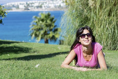 Mujer sonriente joven que pone en un prado verde con una opinión del mar Silla de cubierta en la playa en Brighton Fotografía de archivo libre de regalías