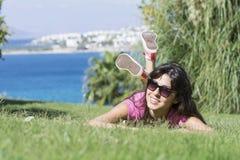 Mujer sonriente joven que pone en un prado verde con una opinión del mar Silla de cubierta en la playa en Brighton Foto de archivo libre de regalías