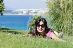 Mujer sonriente joven que pone en un prado verde con una opinión del mar Silla de cubierta en la playa en Brighton Fotos de archivo