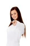 Mujer sonriente joven que señala en la cámara Imagen de archivo libre de regalías