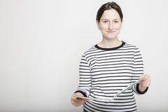 Mujer sonriente joven que se coloca con la revista en sus manos Imagen de archivo