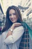 Mujer sonriente joven que se coloca en la calle con los panieres Imágenes de archivo libres de regalías