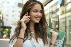 Mujer sonriente joven que se coloca en la calle con los panieres y TA Imagenes de archivo