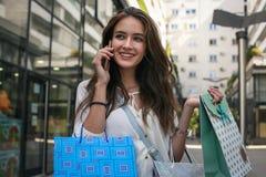 Mujer sonriente joven que se coloca en la calle con los panieres y TA Imágenes de archivo libres de regalías